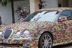 Um automóvel de luxo coberto de carrinhos de brincar